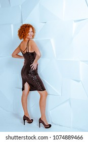 Beautiful sexy smiling woman black short shiny dress and high heels posing in studio. Isolated on white. Full-length portrait. Studio shot. Perfect body shape, make-up