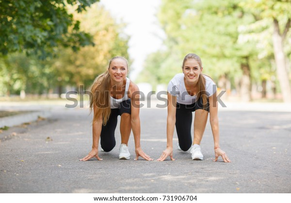 Beautiful, sexy sports girls exercising on a park background. Fitness lifestyle concept. Copy space.