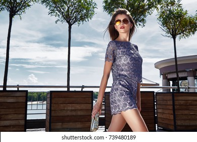 Beautiful sexy  successful woman young brunette wear in stylish fashion skinny blue dress high-heeled shoes and handbag clutch accessory style clothes for a meeting stroll through the summer city.