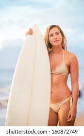 Beautiful sexy surfer girl in bikini on the beach at sunset