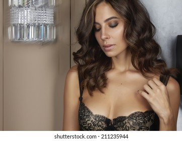 Beautiful sexy tanned brunette woman with curly hair in black lace lingerie with a beautiful evening makeup stands near a wall sconce with eyes drooping lower a little hand strap with shoulder