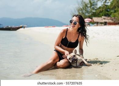 Beautiful sexy tanned girl sitting on the beach on the beach with a dog, laughing and having fun on a tropical holiday vacation, black bikini, sunglasses fashion accessories, french bulldog, lifestyle