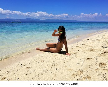 Beautiful and sexy Thai brunette tanned girl in bikini enjoying the crystal clear, turquoise colored ocean and the white sand exotic and tropical beach in Moalboal, Cebu, Philippines