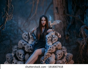 A beautiful sexy vampire woman sits on a throne of the skulls of her victims in a dark mystical forest. Gothic image of the goddess of death with white dragon. dark queen on the hill of skeletons.
