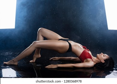 A beautiful sexy wet leggy brunette girl, dressed in black panties and a red bra, sits on the floor and sensually flexes under raindrops in theatrical smoke. Copy space. Advertising design.