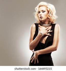 Beautiful sexy white woman in black dress posing at studio