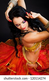 Beautiful sexy woman belly dancer. Arabian oriental professional artist in shining costume with long healthy glossy hair.