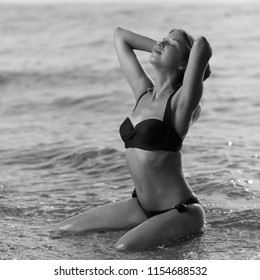 Beautiful sexy woman in bikini posing on beach processed in B&W.