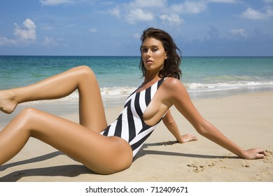 Beautiful sexy woman in bikini posing on beach. Vogue style