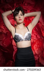 Beautiful sexy woman in black bra and skirt on a background of huge red roses