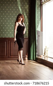 A beautiful sexy woman in a black dress is holding a gun. Mistress, Spy Girl. Assassin