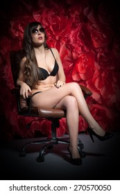 Beautiful sexy woman in black erotic lingerie sitting in an office chair on the background of the huge red roses