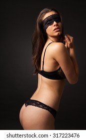 Beautiful sexy woman with black lingerie and lace blindfold.