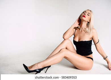 Beautiful sexy woman in black lingerie, in underwear with tan skin and red lips posing in studio on white background. Contrasting retouched shot