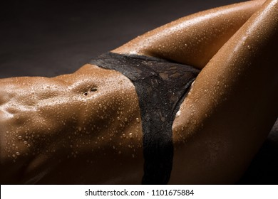 Beautiful and sexy woman body details. Legs and muscular belly, wet skin.