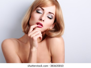 Beautiful sexy woman with bright eyes makeup touching her lips with desire on blue background