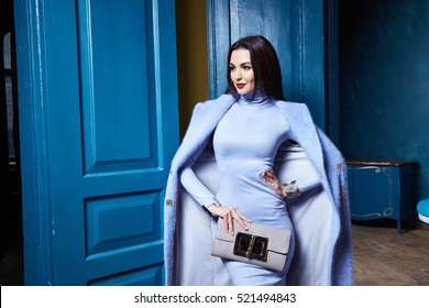 Beautiful sexy woman brunette hair wear fashion clothes business style for office lady trend accessory bag casual glamor natural makeup pretty face interior room door blue color coat jacket outwear.