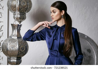 Beautiful sexy woman brunette hair east style arabic morocco furniture glamour model pose fashion clothes silk dress with bow accessory hand bag make up cosmetic pretty face party office room.