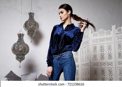 Beautiful sexy woman brunette hair east style arabic morocco furniture glamour model pose fashion clothes skinny denim jeans blue silk blouse accessory hand bag make up pretty face party office.