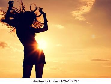 beautiful sexy woman dancing at sunset