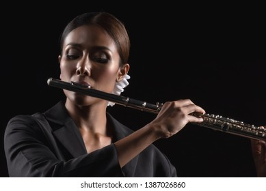 Beautiful sexy woman emotion in dream in music.hold flute on black background, in emotion feeling committed.
