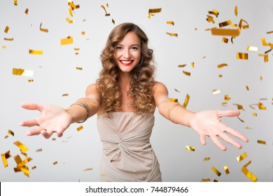 beautiful sexy woman in evening dress celebrating, golden confetti, party, smiling, open arms, inviting, happy