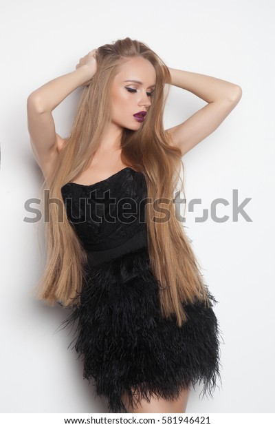 Beautiful sexy woman with fashion make-up and blonde hair in short black dress