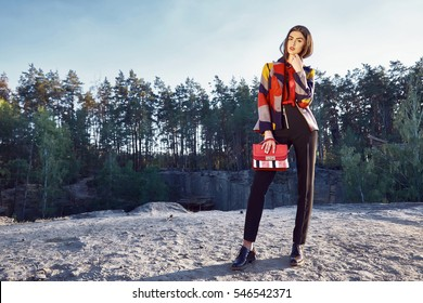 Beautiful sexy woman glamor fashion model female perfect beauty pose wear stylish clothes fall collection pants jacket accessory handbag shoes forest trees nature sun river walk in park romantic date.