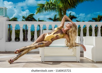Beautiful sexy woman in gold bikini and gold shoes posing on the caribbean luxury hotel.