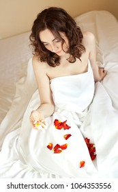 Beautiful sexy woman holding a rose petals in bed (focus on hands)