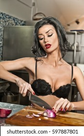 Beautiful and sexy woman in the kitchen. Smiling brunette preparing food. Young girl wearing black bra cutting some onions on the wooden board.cute sensual young woman cutting onion at kitchen.