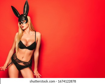 Beautiful sexy woman with large breasts wearing  carnival black mask of Easter bunny rabbit.Hot blonde girl posing near red wall in studio.