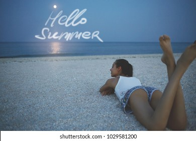 beautiful sexy woman beautiful woman lies on the sand on the beach and looks at the sea and big moon at sunset. Words Hello Summer on the sky backgrond. woman enjoys summer vacation