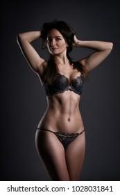 Beautiful sexy woman in lingerie posing on gray studio background, perfect female body, low key studio shot