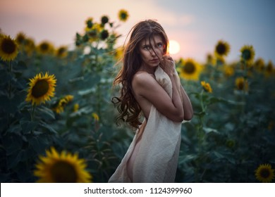 Beautiful sexy woman with long hair in a field of sunflowers in the summer in the sunlight
