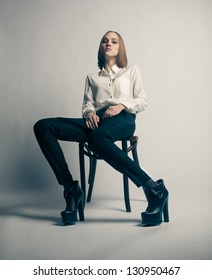 Beautiful sexy woman with long legs sitting at the chair