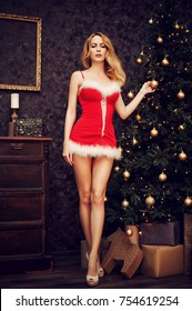 Beautiful sexy woman with long legs and high heels in red christmas santa dress near tree eve with decorations in room