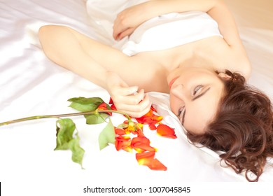 Beautiful sexy woman lying in bed and looking at the rose petals