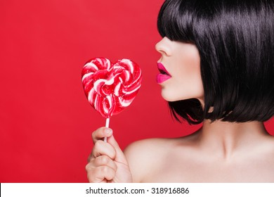 Beautiful sexy woman model with pink lips and lollipop on red background