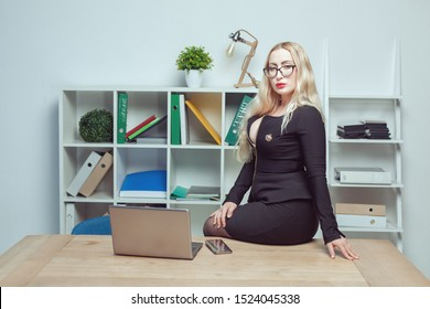 Beautiful sexy woman in office sitting on the desk.