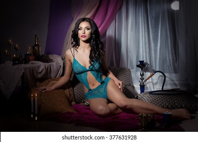 beautiful sexy woman in oriental style with long black hair in beautiful lace lingerie sitting on cushions in a dark room with bright makeup and pink lipstick