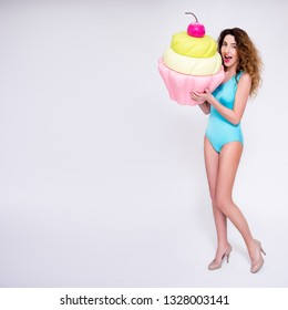 beautiful sexy woman posing with giant cupcake over gray background with copy space