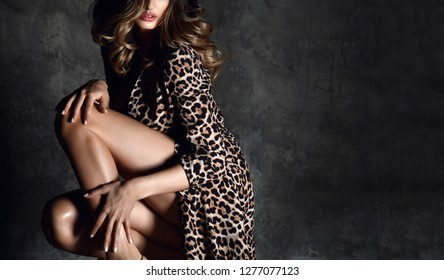 Beautiful sexy woman posing in Leopard print dress on dark  background