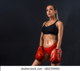 Beautiful sexy woman with red Boxing Gloves with strong abs and body at the gym. Concept about sport fitness martial arts on a dark modern background.  Fashion studio photo of sexy athletic woman