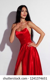 Beautiful sexy woman in red elegant evening dress and ruby crown posing against white background. Fashion style portrait of glamorous model