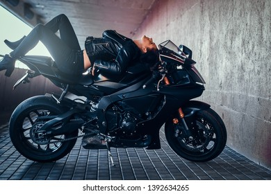 Beautiful sexy woman is relaxing on her motobike in quiet tunnel.
