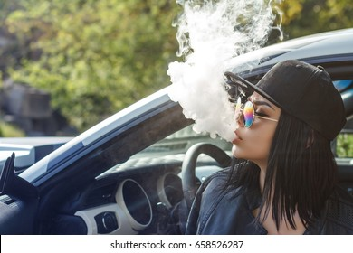 Beautiful sexy woman is sitting in the car and vaping .Cloud of vapor.