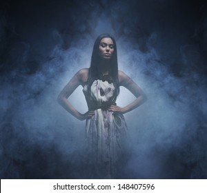 Beautiful and sexy woman standing in the darkness