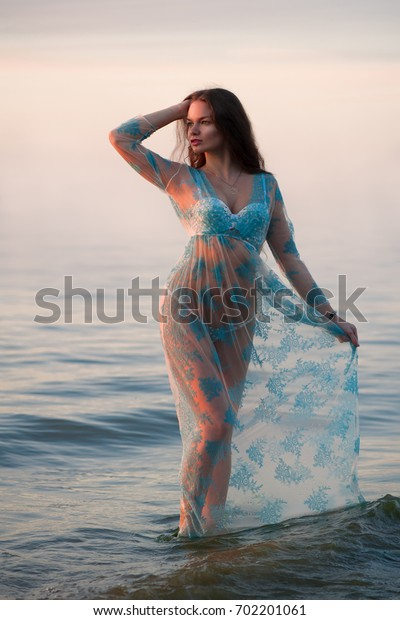 Beautiful sexy woman standing on the sea shore