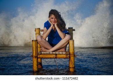Beautiful and sexy woman staying on a old chair and  big waves are in the background from the ocean.